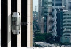 The external lift (elevator) on the Pan Pacific hotel in Singapore. The central financial district is in the background. - Stock Image