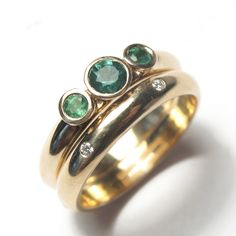 Pair of gold rings using customers own mix of gold and set with emeralds and diamonds.