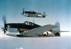 Two U.S. Navy Grumman F6F-3 Hellcats in tricolor camouflage, sea blue, intermediate blue and insignia white.