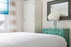 white bedroom with mint green dresser, pantone lucite green, gray mirror frame