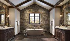 stone walls behind bathroom vanities and sinks, dark wood cabinets, marble countertop, sconces, dark wood ceiling beams. freestanding white bath tub