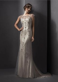 Twenties Vintage romance is found in this gorgeous sheath gown, comprised of luxurious Palatzo satin with glamorous tulle overlay, accented with glittering Swarovski crystals. Complete with illusion neckline and finished with covered button and zipper back closure. Colors available ivory, champagne (shown)