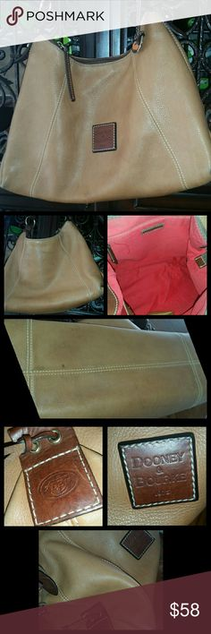 """Dooney & Bourke Leather Hobo in cognac & brown Used condition but still has a lot of life left.  This is a beautiful soft leather Dooney & BourkeLeather Hobo. Gorgeous cognac color with Brown leather accent and trim leather .  Signature hang-tag, interior slip pocket. Could use professional cleaning.  Pictures show light wear and some discoloration to the exterior, interior is stain free other than very faint pen mark. Corners have some wear  Measures 15"""" L x 5"""" W x 10"""" H with 9"""" Drop Dooney…"""