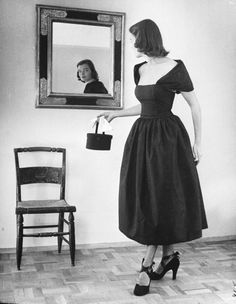 A model wearing a black moire evening dress. Photograph by Nina Leen. USA, 1947.