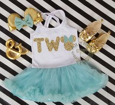 2pc Mint and Gold Glitter Minnie Two Year Old Birthday Tutu Dresses For Toddler GirlsLet us add a little or a lot of shine to your little birthday angel's life with our New and Exclusive glitter minnie inspired two year old birthday tutu dresses. This tutu dress makes the perfect minnie themed birthday outfit! Designed with a gold glitter two with mint bow on a fluffy mint tutu dress. Your little one will definitely be the sparkle in your eye on their very special day. Glitter does not co...
