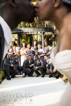 Super cute shot of bride and groom kissing in the foreground with the bridal party in the background, very unique bridal party photo.