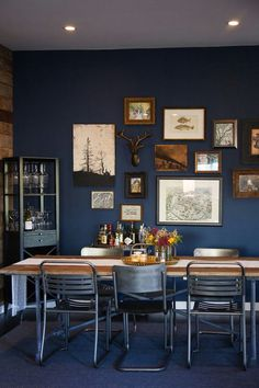 dramatic blue dining room with a rustic wall gallery | farmhouse table with mismatched chairs | small bar cart