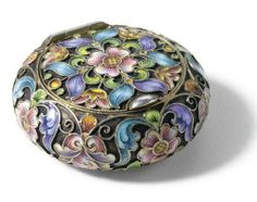 A Fabergé silver-gilt and cloisonné enamel pill box; workmaster Feodor Rückert, Moscow, Circular cushion form, the surface is painted with shaded polychrome enamel flowers on a stippled ground, 88 standard.
