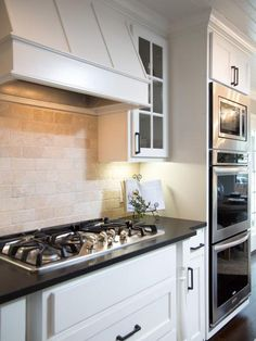A+wood-wrapped+vent+hood+tops+off+a+new+high-end+gas+range+and+stone+tile+backsplash.