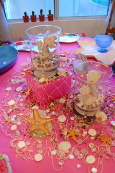 Hawaiian themed graduation party. Fishnet and seas shells. Also found Precious Moment mermaids on Ebay and added glass jars