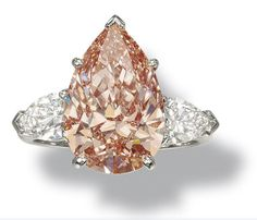 Rare Fancy Intense Orangy Pink Diamond Ring, Graff       Claw-set with a fancy intense orangy pink pear-shaped diamond weighing 5.57 carats, between pear-shaped diamond shoulders mounted in platinum. Diamond is Fancy Intense Orangy Pink, natural color, internally flawless.  (Sold for $939,200)