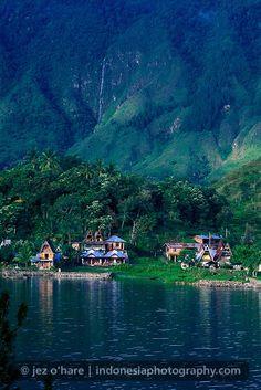 Tuk Tuk village & waterfall, Samosir Island, Lake Toba, North Sumatra, Indonesia.  35m natural waterfalls and traditional architecture roof batak