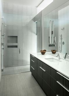 This bathroom has a glass enclosed shower with built-in shelving.