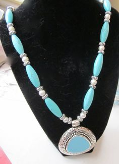turqoise necklace with white pearls and silver spacers measures 24 inches in lenght  cost 25.00$