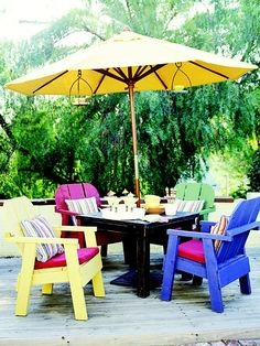 Unify furnishings in a spectrum of colors with the accessories you choose. Chairs painted in primary colors pull together as a dining set when they share solid red cushions and rainbow-stripe pillows.