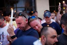 Paul Cox, right, leans on the shoulder of Brian Sullivan, as they observe a moment of silence during... - David Goldman/AP Images