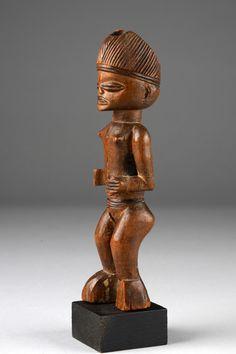 Weibliche Zauberfigur D. R. Kongo, Chokwe Holz, braune Patina, Brandzier, Frisur mit Bohrloch, in das ursprünglich wohl ein Horn eingesteckt war, min. best. (Hände), Risse, Fehlstellen (linker Fuß), Sockel; die Figur repräsentiert eine weibliche Ahne, die als Hilfsgeist für einen Wahrsager fungierte. Durch magische Ladung, die in die Öffnung am Kopf eingefügt wurde, wurde der der Figur innewohnende Geist aktiviert. Das jetzt fehlende Horn diente als Verschluss und sollte die Kräfte in der…