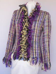 Vistosa composición de bullones en tonos violetas boreales decoran el peto de esta chaqueta. Flecos de fieltro y diversos géneros rematan su contorno.   Medidas: talla 46  Técnica: telar manual  Hilados: algodón, seda, lurex y vellón  Géneros: seda, gasa, satén