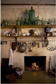 Wonderful collection of bottles, jars, china, sitting on two wood shelves with cooking utensils hanging on iron rod above the kitchen fireplace via:Moon to Moon: Creating a Bohemian kitchen.