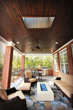 Covered porch, complete with brick columns, v-groove ceiling, skylights, built-in gas grill, tile flooring, ceiling fan, and a linear fire pit.