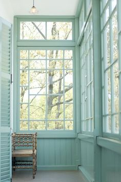 transom windows, with woodwork painted a soft and minty turquoise hue