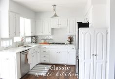 a classic white kitchen with marble countertops & white subway tile