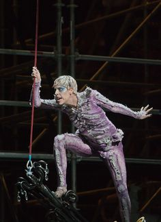 This Ariel comes from an opera version, and he isn't the glamorous lady or the non-threatening spirit. There's something kind of creepy about the actor's expression, and the costume looks a lot like a skeleton. Purple would stand out on stage, versus the pale body paint and skimpy clothes seen on other Ariels.