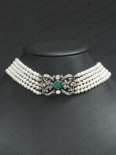 A pearl choker with a 19th century silver, diamond and emerald plaque/brooch.