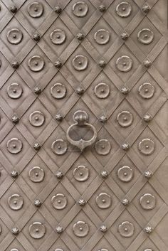 The main door to Karlstein Castle in the Czech Republic is covered with ornate iron decorations in a traditional and functional style with c...