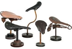 """Group of five vintage bicycle seats and saddles mounted on pulley bases for display. 1. Antique Troxel beige leather seat with chrome crash rail. 2. Antique early 1900s rusty seat frame with springs. Unknown manufacturer. 3. Vintage Wright's leather saddle. From England. 4. Vintage Cionlli ribbed leather saddle seat. Appears to have been painted at one time. 5. Not-so-vintage Kashimax Aero Saddle seat. From 10""""-20""""H."""