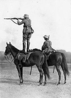 A German soldier firing a gun from the back of his horse. [1939]
