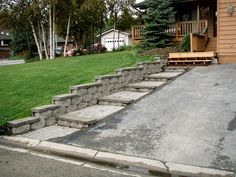 This looks disjointed. The asphalt drive + wood stairs + flat pavers + pavers = busy.  I don't like the gray pavers with brown house.