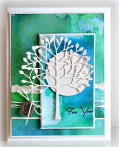 By Birgit Edblom (Biggan at Splitcoaststampers). Background is paper sprayed with Dylusions ink spray. Note the cuts & the layers, all adding interest to the card. Die-cut circle for sun/moon. Die-cut arboscello tree from Memory Box.