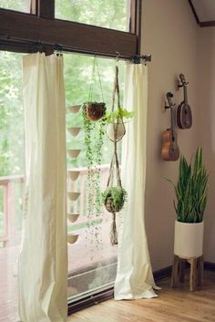 Hanging rope/macrame plant hangers from curtain rods in front of windows.