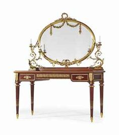 A FRENCH ORMOLU-MOUNTED MAHOGANY TABLE COIFFEUSE BY FRANÇOIS LINKE, PARIS, CIRCA 1900. With ovoid mirror flanked by foliate candle branches over a rectangular top and three frieze drawers.