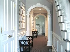 Gorgeous hallway...archways, doors, wainscoting, benches, wall art.