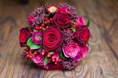 Hand tied wedding bouquet of grand prix and hot lady roses, with red and pink ranunculus and red skimmia - ideal for a winter wedding