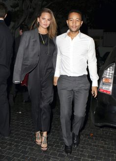 The beauty of a jumpsuit is that it's as easy-to-wear as it is stylish. Teigen adds even more flair by stealing John Legend's suit jacket and wearing it on her shoulders. (Always a good way to add a little something/keep warm, in a pinch.)   - MarieClaire.com