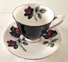 For your consideration is a beautiful vintage tea cup and saucer by Royal Albert with the Masquerade pattern of an elegant rose, made in England. It is white and black with a black and burgundy rose accentuated with silver trim. Both the cup and saucer are in excellent condition