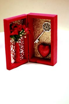"""This tiny 4.5"""" x 2.4"""" mini shrine is a charming addition to your altar for working with the energy of passion, love and romance. Key represents the """"key to the heart."""" A miniature vase of fabric roses"""
