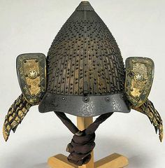 62 plate shiinari (acorn-shaped) za-boshi suji bachi kabuto by Saotome Iyetada, 18th c, iron bowl with standing rivets [hoshi] randomly spaced in groups of one, two and three, a tosei mabisashi [peak] is held by five za boshi [rivets with shaped washers], the lower half of the front of the helmet gilded, tehen kanamono, itamono jikoro [solid plate neckguard] unusually laced in groups of dark blue, red and mixed and colour lacing, fukigayeshi leather covered with gilded fukurin and mon.