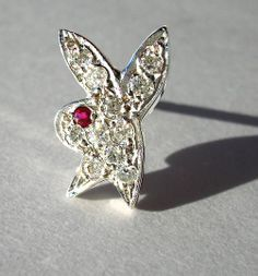 'playboy-bunny' pin, handmade from18k white gold, set with diamonds and ruby.