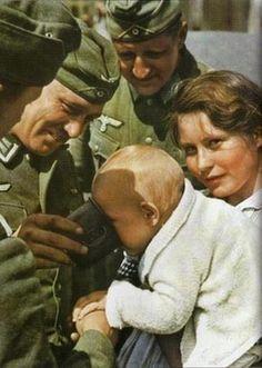 Wehrmacht soldiers feeding a Ukrainian child, 1941.