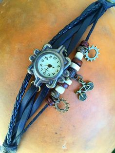 """Is it time to go ride yet? Count the hours down till your next ride with this fun beaded watch with bicycle and gear charms. - Black leather strap with snap closure - Adjusts to fit wrists 6 3/4"""" to 7"""