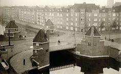 Op de brug tussen de Ferdinand Bolstraat en de Scheldestraat aan de Oude Amstelkade zijn op de vier hoeken ervan in huisjes winkels gevestigd. Nederland, Amsterdam, 1928.