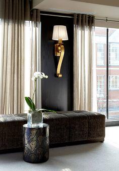 black walls, seating against wall / window. black, gold, grey living room. dark…