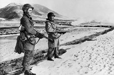 With the frozen Yalu River and snowy Manchurian hills at their backs, Cpl. Mayford J. Gadner, left, and Pfc. Tommie Robinson from New Mexico, stand guard near Hyesanjin on Korea's northeastern front, Dec. 2, 1950. The GIs are members of the U.S. 7th Division. (AP Photo)