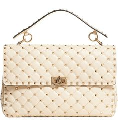 Signature goldtone pyramid studs accentuate the quilted lambskin of this perfectly proportioned shoulder bag that balances vintage elegance with rocker-chic edge.