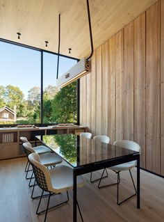 Bates Masi's Office in East Hampton: Now a True Extension of the Firm's Style. Wood panelling serves as a backdrop for a conference table.