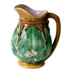 George Jones Majolica Pitcher  PRICE:$1,700 Purchase  CREATOR:George Jones (Designer) PLACE OF ORIGIN:England DATE OF MANUFACTURE:19th century PERIOD:20th Century MATERIALS AND TECHNIQUES:Majolica MATERIALS NOTES:Majolica CONDITION:Excellent HEIGHT:8.5 in. (22 cm) WIDTH:7 in. (18 cm)George Jones Majolica Pitcher
